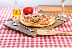 Pizza som tjänas som på gammalt träbräde royaltyfri foto