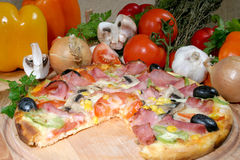 Pizza. A pizza and some ingredients Stock Photo