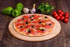 Pizza sottile con il prosciutto ed i pomodori fotografie stock