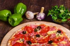 Pizza sottile con il prosciutto ed i pomodori fotografia stock