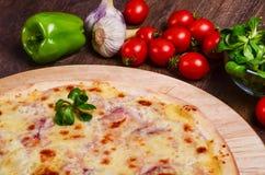 Pizza sottile con il prosciutto sotto formaggio fotografie stock
