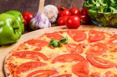 Pizza sottile con la margarita dei pomodori immagine stock