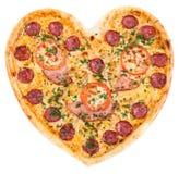 Pizza sous forme de coeur avec des tomates, spri de jambon et de salami Images libres de droits