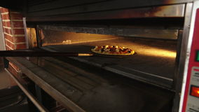 Pizza on a special shovel is put in the oven stock footage