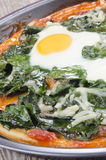 Pizza with spinach and fried egg Stock Image