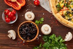 Pizza still life. Freshly baked pizza and its components arranged on wooden background. Pizza still life. Freshly baked Italian pizza and its components stock photography