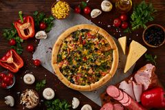 Pizza still life. Freshly baked pizza and its components arranged on wooden background. Pizza still life. Freshly baked Italian pizza and its components stock photos