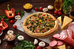 Pizza still life. Freshly baked pizza and its components arranged on wooden background. Pizza still life. Freshly baked Italian pizza and its components royalty free stock image
