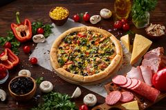 Pizza still life. Freshly baked pizza and its components arranged on wooden background. Pizza still life. Freshly baked Italian pizza and its components royalty free stock photo