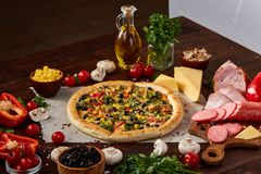Pizza still life. Freshly baked pizza and its components arranged on wooden background. Pizza still life. Freshly baked Italian pizza and its components stock photo