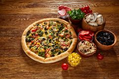 Pizza still life. Freshly baked pizza and its components arranged on wooden background. Pizza still life. Freshly baked Italian pizza and its components royalty free stock photos