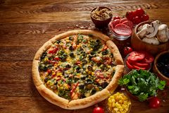 Pizza still life. Freshly baked pizza and its components arranged on wooden background. Pizza still life. Freshly baked Italian pizza and its components royalty free stock images