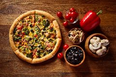 Pizza still life. Part of freshly baked pizza and its components arranged on wooden background. Pizza still life. Part of freshly baked Italian pizza and its stock images