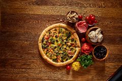 Pizza still life. Part of freshly baked pizza and its components arranged on wooden background. Pizza still life. Part of freshly baked Italian pizza and its royalty free stock photo