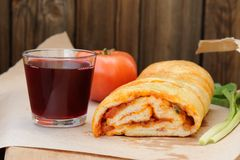 Pizza stromboli cut with glass of red wine, fresh scallion and t Stock Photos