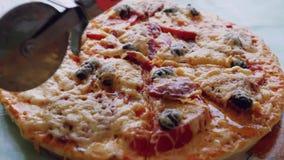 Pizza sul taglio manuale del bordo di legno del piatto con la taglierina della pizza 1920x1080 HD stock footage