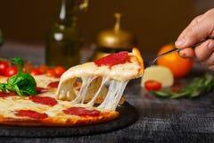 Pizza sulla tavola che allunga formaggio con cuscus tagliato immagine stock