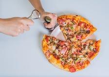 Pizza sulla tavola con la mano delle ragazze Fotografia Stock
