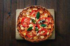 Pizza sulla tavola di legno, vista superiore Immagini Stock