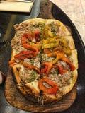 Pizza sur la planche à découper en bois Photos stock