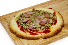 Pizza sur une planche à découper Image stock