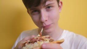 Pizza Szczęśliwa nastoletnia chłopiec je plasterek pizzy pojęcie nastoletni chłopak głodny je plasterek pizza zwolnionego tempa w zbiory wideo