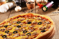 Pizza on the table. Pizza with mushrooms on the kitchen table along with spices and wine bottle Stock Image