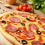 Pizza on the table. Pepperoni pizza with cherry and paprika on the kitchen table Royalty Free Stock Image