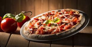 Pizza on the table. Pizza with bacon on the wooden table royalty free stock image