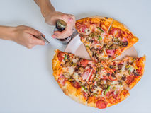 Pizza on the table with girls hand Stock Photo