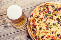 Pizza on the table. With a glass of beer stock photos