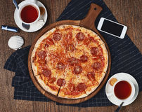 Pizza on table. Pepperoni pizza standing on wooden table served with black textile napkin. Two cups of black tea and smartphone lying table surface. Flatlay stock photography
