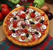 Pizza. Tasty pizza with bacon, mushrooms and tomato souce Royalty Free Stock Image