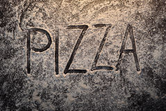 Pizza text on flour top view stock photography