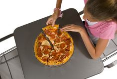 Pizza Time. Young girl eating pizza with white background royalty free stock images