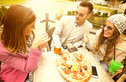 Pizza time. Young group of laughing people eating pizza and having fun.They are enjoying eating and drinking together Royalty Free Stock Photos