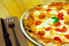 Pizza am Tisch Lizenzfreie Stockbilder