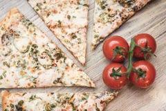 Pizza, tomates de cereja em um fundo de madeira claro fotografia de stock