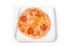 Pizza with tomato and cheese in a white plate on an isolated white background stock photo