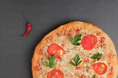 Pizza with tomato and red chili on grey table, top view and place for text royalty free stock images