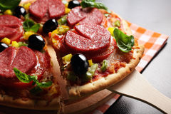 Pizza with tomato, salami, olives and basil. Hot, delicious, juicy, fresh-cooked pizza Stock Photos
