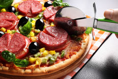 Pizza with tomato, salami, olives and basil. Hot, delicious, juicy, fresh-cooked pizza Royalty Free Stock Image