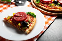 Pizza with tomato, salami, olives and basil on a plate. Hot, delicious, juicy, fresh-cooked pizza Stock Image