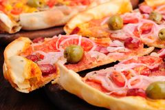 Pizza with tomato, salami, peppeeoni, olives and Royalty Free Stock Photos