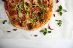 Pizza with tomato sauce, prosciutto and arugula. Perfect healthy lunch idea: Pizza with tomato sauce, prosciutto and arugula royalty free stock photography