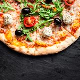Pizza with tomatoes, mozzarella cheese and arugula. Pizza menu.Top view with copy space on dark stone table royalty free stock images