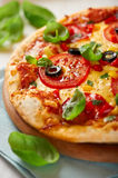Pizza with tomatoes, pepper and salami Stock Photo