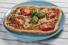 Pizza with tomatos. Pizza with tomatoes on a blue plate Royalty Free Stock Photography