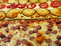 Pizza topping. Pizza with cheese, tomatoes, sausage, pepperoni, ham, salami and other fresh ingredients. Real Italian restaurant - pizzeria. Eating out. Venice Stock Images