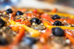 Pizza topping detail. Pizza detail with olives and vegetables topping royalty free stock photography
